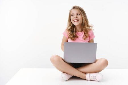 Sorglos fröhliches, blondes, kaukasisches süßes Kind, junge Schwester, die mit Laptop auf dem Boden sitzt, freudig lacht, online lernt, digitale Bildung, wegschauen, den linken Kopienraum wegsehen, glücklich lächeln, neue Sprache lernen