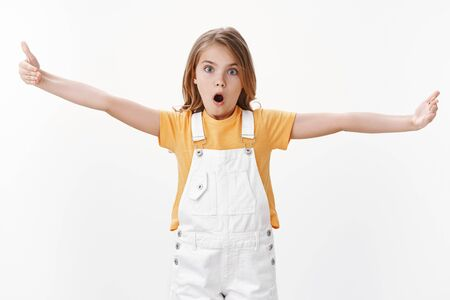 Impressed fascinated cute clever blond girl explain something big, stretch hands showing huge enormous vast product, open mouth and stare camera thrilled, standing speechless white background