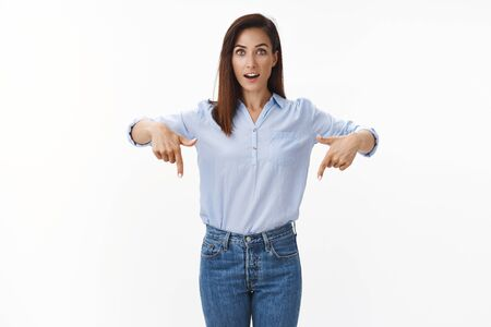 Amused adult female entrepreneur wonder new product, look questioned admired, pointing fingers down, asking question interested about bottom promo, stand white background curious, smiling upbeat