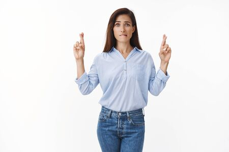Nervous cute worried adult woman with tattoo arm, bite lip anxious, cross fingers good luck, willing win lottery, concerned awaiting important result, praying fortune, supplicating white background