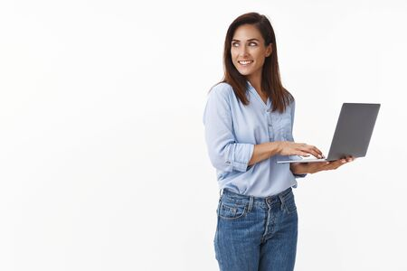 Attractive smart adult woman freelancer, entrepreneur working laptop, hold device turn left copy-space amused, smiling curiously observe product, working, typing client feedback, white background
