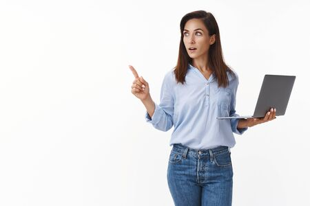 Smart creative busy female entrepreneur giving directions employees manage business, hold laptop, working, pointing aside copyspace, eureka gesture, turn left, have idea, stand white background Фото со стока