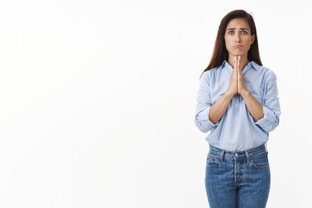 Uneasy cute innocent adult brunette woman asking apology, hold hands pray, pull sad gloomy face, frowning begging mercy, pretty please, asking favor, need lend money, stand white background