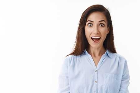 Amused cheerful adult 30s housewife look impressed, open mouth fascinated surprised, smiling excited, participate interesting event, stare camera wondered enthusiastic, white background