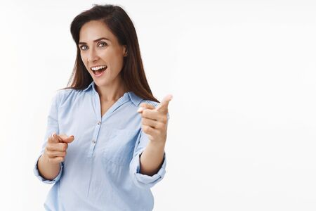 Lucky smiling ambitious middle-aged businesswoman feeling motivated successful, triumphing win, pointing you camera, making choice, congratulate friend good decision, stand white background