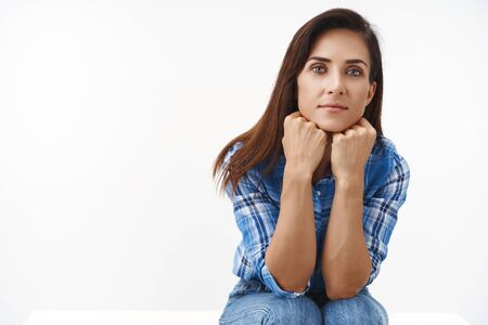 Tender lovely middle-aged sensual woman, sit table in white office, lean head hands, joyfully look camera, smiling cute entertained, gazing thoughtful and curious, listen interesting story