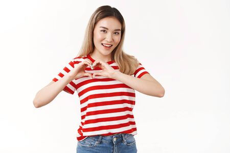 Optimistic sassy good-looking asian blond girl show heart sympathy gesture smiling toothy energized enjoy summer love girlfriend cherish romantic beautiful relationship, standing white background Stok Fotoğraf