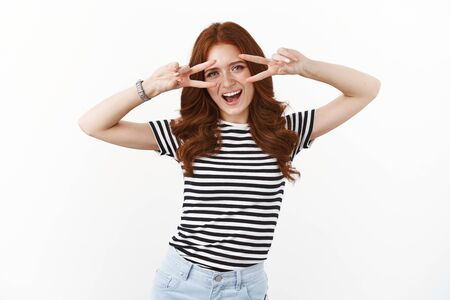 Sassy good-looking european redhead girl in striped summer t-shirt having fun, fool around show peace, victory signs over eyes, smiling amused open mouth excited, posing for holiday photo Stock Photo