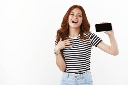 Grateful and flattered cute redhead girl in striped t-shirt, showing smartphone display horizontally, touching chest thankful and touched, smiling happily, laughing and gazing camera 免版税图像