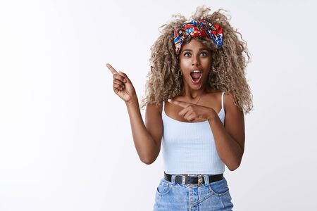 Impressed, stunned african-american curly-haired blond female with stylish hipster headband, open mouth gasping amazed, pointing left astonished with cool awesome promo, white background Stock Photo