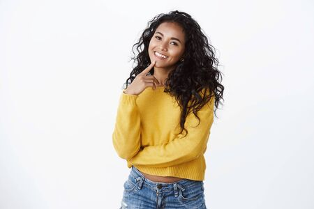 Lovely modern curly-haired female student in yellow sweater, tilt head silly and smiling camera, touch lip thoughtful, inspirational mood, checking out interesting offer, white background