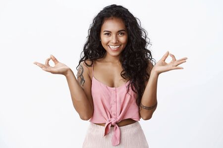 Relaxation, yoga and happiness concept. Attractive curly african-american tattooed girl in stylish pink top smiling joyfully, show zen or meditation gesture as relieve stress, calm down, feel perfect