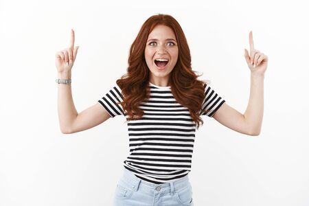 Enthusiastic thrilled young amused redhead woman dropping jaw astonished and surprised, look camera adoration and fascinated, tempting try out new product, pointing up, white background