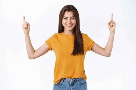Cheerful, attractive woman in yellow t-shirt smiling and friendly showing interesting promo event, pointing raised fingers up, grinning, give advice what page visit, recommend participate event