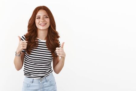 Cool stylish and cheeky redhead caucasian woman in striped t-shirt give thumbs-up, support friends choice, smiling nod acceptingly, agree decision awesome, stand white background satisfied