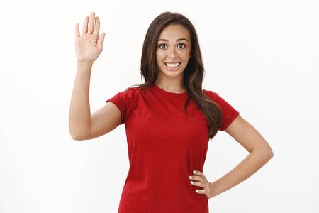 Friendly cute brunette girl in red t-shirt raising hand up, waving palm saying hello, greeting nicely newcomers, invite guests with warm welcome, standing white background, say bye