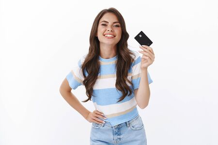 Finance, banking and money concept. Carefree unbothered good-looking stylish woman like paying credict card, smiling joyfully recommend open bank account, give card to make purchase Stock Photo