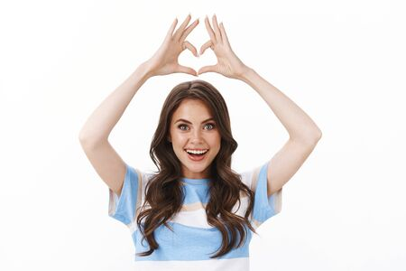 Waist-up cute tender modern glamour woman with tattoo look astonished and excited raise hands above head show heart, love gesture adore new store, confess sympathy, stand white background