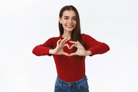 Friendly good-looking brunette woman absolutely in love with new cosmetics product, showing heart sign, confess, admire or cherish something, smiling as look camera tenderly, white background