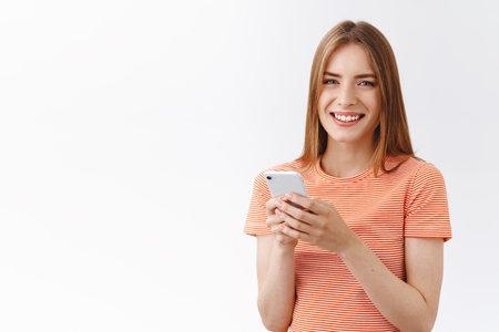 Sympathique, jolie jeune femme insouciante en t-shirt rayé tenir un smartphone, souriante et regardant la caméra ravie, naviguant sur Internet, passant un appel téléphonique, envoyant une histoire drôle par SMS, se tenant sur fond blanc