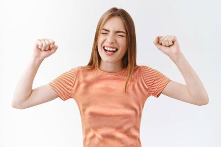 Lively, cheerful good-looking caucasian woman in striped t-shirt, rooting and yelling from amazement and joy, feeling freedom and happiness, fist-pump with smile and closed eyes, triumphing