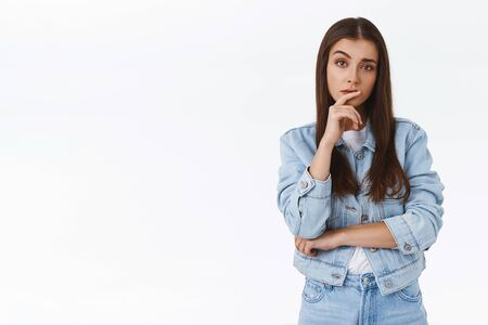 Skeptical, suspicious serious-looking thoughtful caucasian girl in denim jacket, touching lip and raising one eyebrow suspicious, have doubts, suspect someone, thinking, searching solution