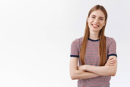 Cheerful friendly girl with long hair, wear striped t-shirt, hold hands crossed chest, casual relaxed pose, tilt head and smiling look enthusiastic, having interesting conversation, white background