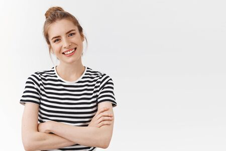Waist-up shot lucky, confident good-looking woman with messy bun in striped t-shirt, cross hands chest, tilt head and smiling looking like professional, being self-assured and encouraged