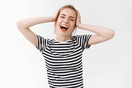 Waist-up shot carefree, lively emotive young woman with messy bun in striped t-shirt, smiling singing and enjoying beautiful day, feeling relaxed and delighted, touch head dancing, white background Stock Photo