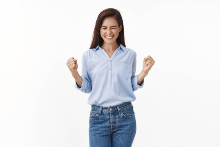 Triumphing happy brunette middle-aged woman receive excellent news, got promotion, fist pump delighted, close eyes smiling broadly, celebrating, win lottery, do victory dance, white background Stok Fotoğraf