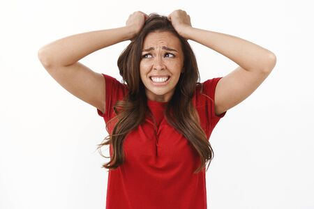 Girl in huge trouble panic. Shocked upset brunette woman pull hair from head, grimacing in sorrow and disappointment, frowning crying from troublesome problematic situation, white background