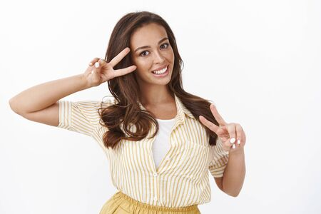 Waist-up shot silly enthusiastic young female posing playfully and coquettish over white background, showing goodwill, make victory peace gesture, smiling broadly. Wellbeing concept