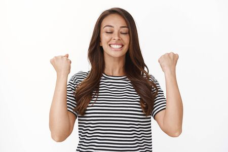 Relieved happy female athlete receive sport results, feeling accomplished and delighted, fist pump, breathing happily and smiling, triumphing, celebrate success, winning competition