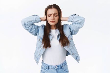 Stop hurting my feelings. Troubled fed-up young woman close her ears, cant hear lies and see betrayal anymore, close eyes, standing depressed and upset, unwilling listen, standing white background