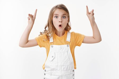 Amused pretty excited blond girl, little child showing you amazing thing, raise hands up, pointing top copy space, pouting stare astonished, say wow thrilled explain inredible fantastic promo