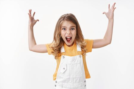 Angry little girl losing temper arging, raise hands full dismay and disappointment, complaining stare anger and displeased, shouting furious bothered, stand white background arguing