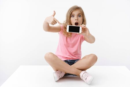 Joyful pretty amused teenage blond girl with cute surprised expression sit on floor, show blank smartphone screen, pointing mobile phone, discuss amazing cartoon episode open mouth astonished