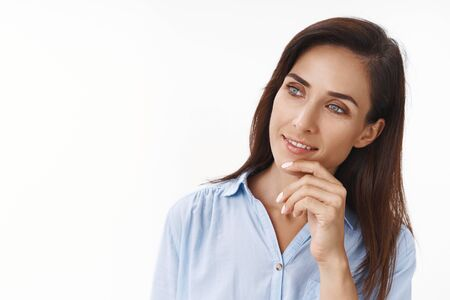 Close-up curious pleased businesswoman listen employee ideas during meeting, tilt head touch chin intrigued, smiling looking copy space left side satisfied smile, taking decision, white background