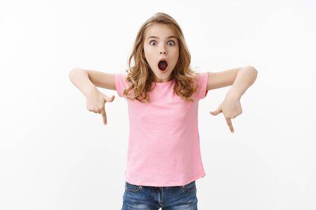 Charismatisch erstauntes süßes blondes europäisches Mädchen in rosa T-Shirt, unglaubliche Dinge erklären, erstaunt und aufgeregt aussehen, offener Mund schreien beeindruckt, nach unten zeigend, untere Promo anzeigen