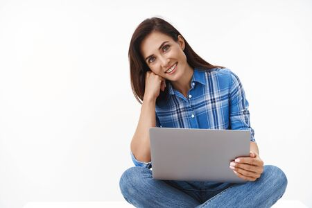 Tender lovely middle-aged brunette woman sit crossed legs, hold laptop, tilt head smiling joyfully camera, use computer, browsing internet, relaxing watching movie co-working space, white background 版權商用圖片