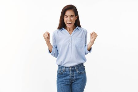 Happy triumphing good-looking adult woman feel excitement and joy hear lucky news, fist pump celebrating victory, smiling broadly, close eyes, unbelievable positive result, winning, white background