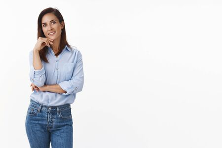 Joyful carefree adult female smiling friendly, stand casual relaxed pose blue-collar shirt, touch face tilt head, look interested delighted hear interesting conversation, stand white background