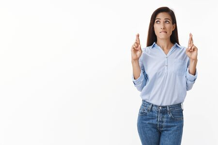 Worried female office worker awaiting important decision take, cross fingers good luck, bite lip nervously, look left hopeful, praying dream come true, make wish, anticipating win good news