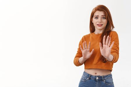 Awkward and unimpressed cute redhead female model in orange cropped top, raising hands defensive in stop, please no gesture, smiling thanking for offer but rejecting, give refusal, white background