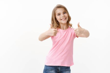 Optimistic happy cheerful young blond girl, daughter thank dad for great awesome present, show thumbs up approval and like gesture, smiling joyfully, accept cool gift, stand white background Reklamní fotografie