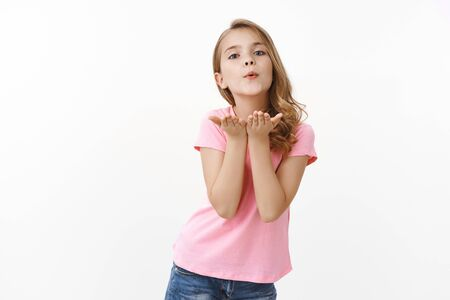 Tender lovely caucasian blond girl in pink t-shirt blowing air kiss with hands near pouted lips, smiling silly send love, confess sympathy standing white background upbeat Stock Photo