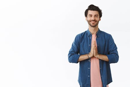 Relieved, happy good-looking relaxed guy practice yoga or meditating, standing straight with hands clasped near chest in namaste gesture, smiling grateful, thanking for help, white background