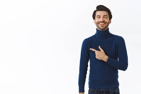 Proud successful good-looking bearded businessman in blue stylish high neck sweater, pointing left and smiling with satisfied expression, laughing as bragging bought brand new car, white background Foto de archivo - 138299844