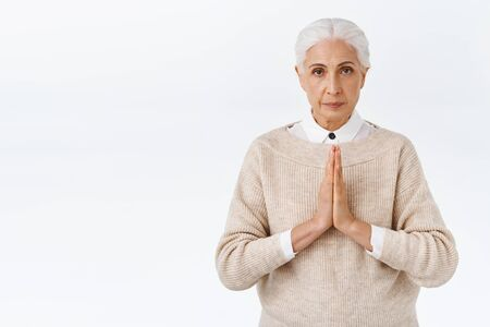 Serious-looking determined and patient old woman, senior lady with grey combed hair, press palms together over chest in supplication gesture, praying, begging someone, stand white background Zdjęcie Seryjne