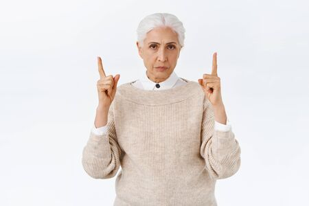 Disappointed, angry gloomy senior lady with grey combed hair, frowning and sulking, pointing fingers up at terrible banner, dissatisfying scene, demand answers, feel frustrated, white background Imagens